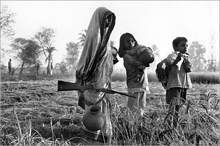 A woman emerges out of hiding for the first time, carrying a rifle and accompanied by her children. The family were hiding from Pakistani troops during the Bangladesh War of Independence in 1971. Photo: Penny Tweedie
