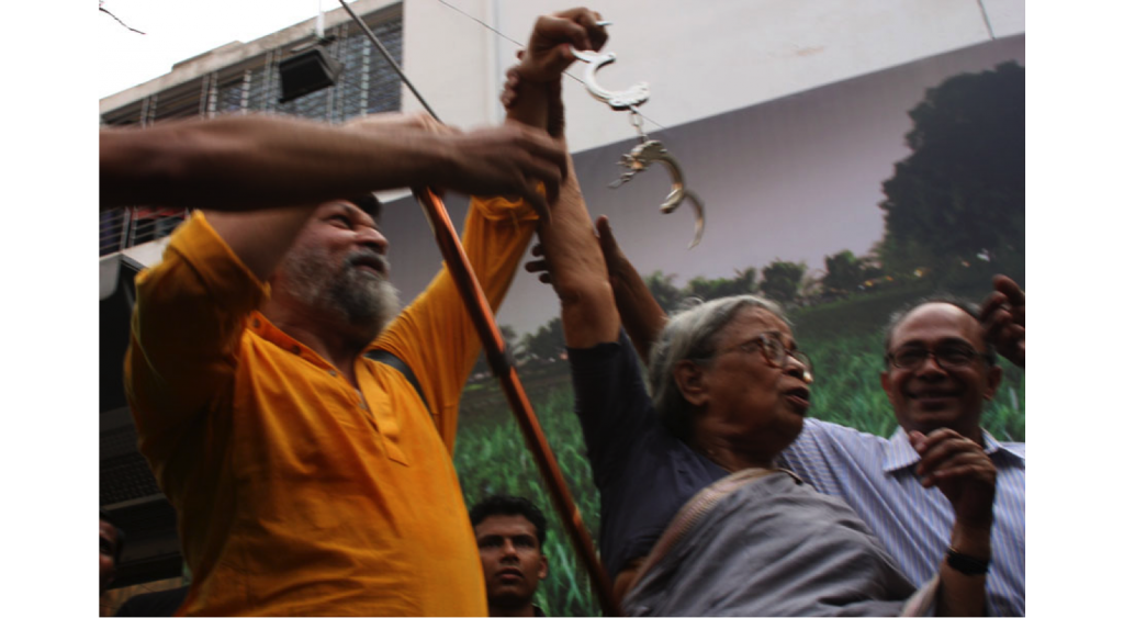 "Mahasweta Devi removing handcuffs from Shahidul Alam at symbolic opening of ""Crossfire"" exhibition outside Drik. Photo: Drik"